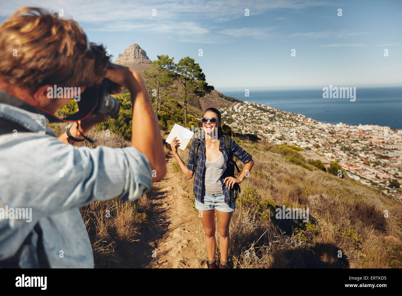 Young man taking photos of pretty girlfriend showing a map in countryside while trekking during summer vacation. - Stock Image