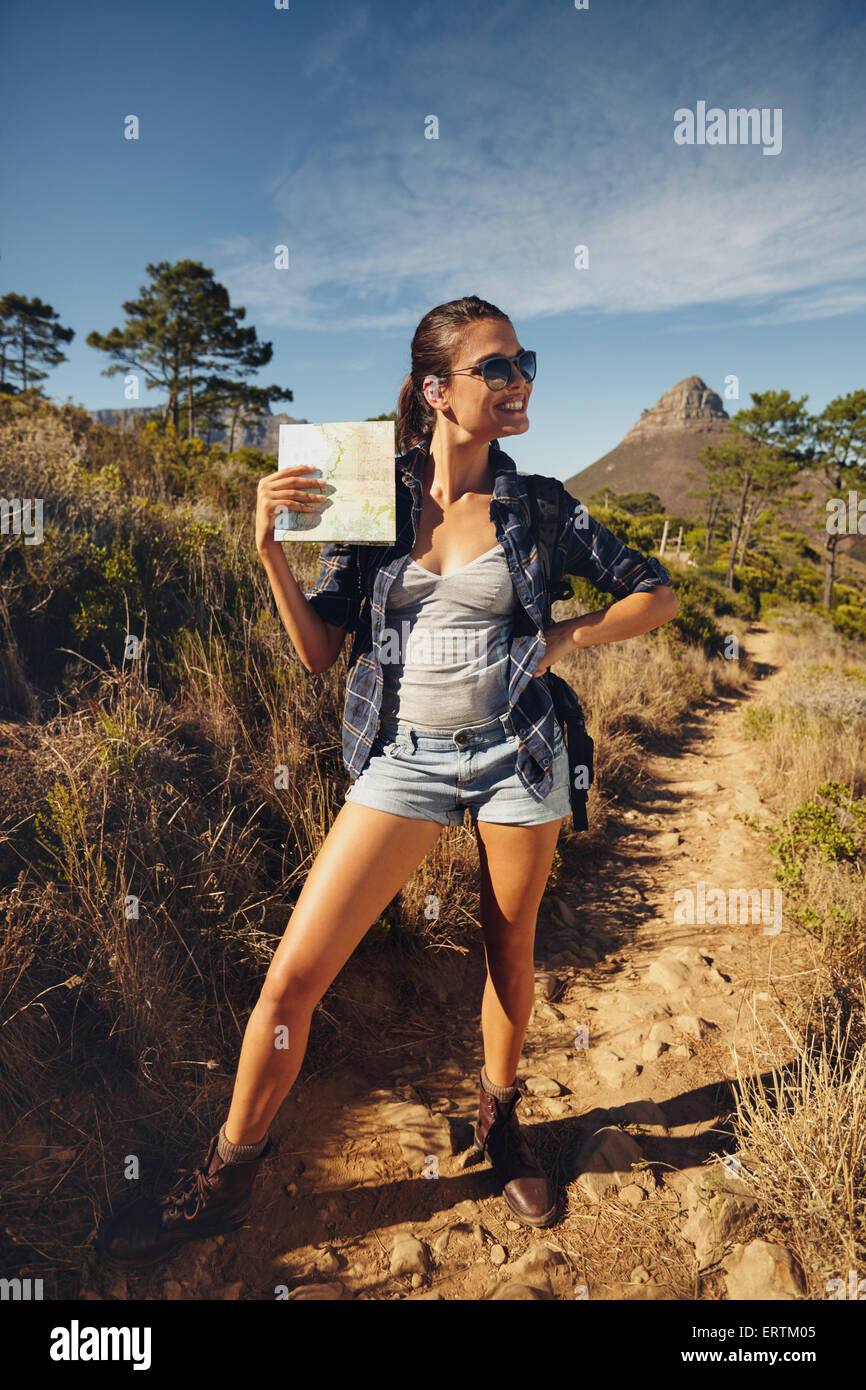 Portrait of beautiful young woman posing with a map outdoors. Caucasian woman hiking in a summer day, looking away - Stock Image