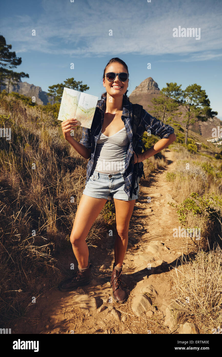Full length portrait of beautiful young woman outdoors posing for camera showing a map. Caucasian female hiker on - Stock Image