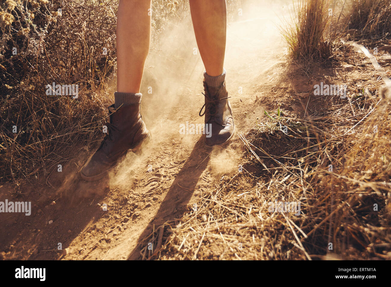 Young woman's feet as she hikes on a mountain trail with puff of dust. Woman hiking on dirt path in countryside. Stock Photo