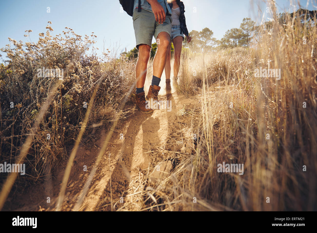 Low angle view of young couple walking on country trail path. Couple hiking on mountain coming downhill. Cropped - Stock Image