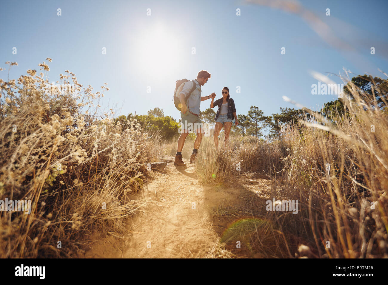 Outdoor shot of young couple on hiking trip, walking on dirt trail in mountains holding hands. Young man and woman - Stock Image