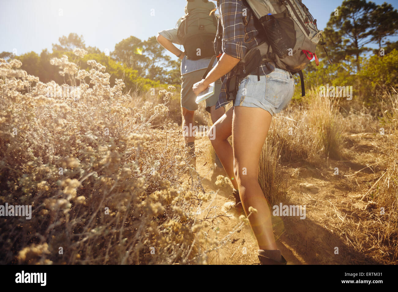 Cropped image of man and woman walking on country trail path. Young couple hiking on mountain on sunny day. - Stock Image