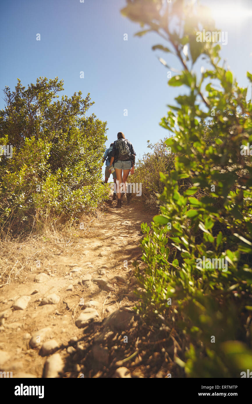 Image of people walking through mountain trail. Rear view shot of couple hiking on dirt path through grass and plants - Stock Image