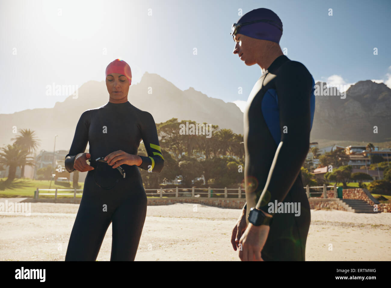 Shot of young man and woman with their swimming gear on standing on the beach. Triathletes preparing for the race. - Stock Image