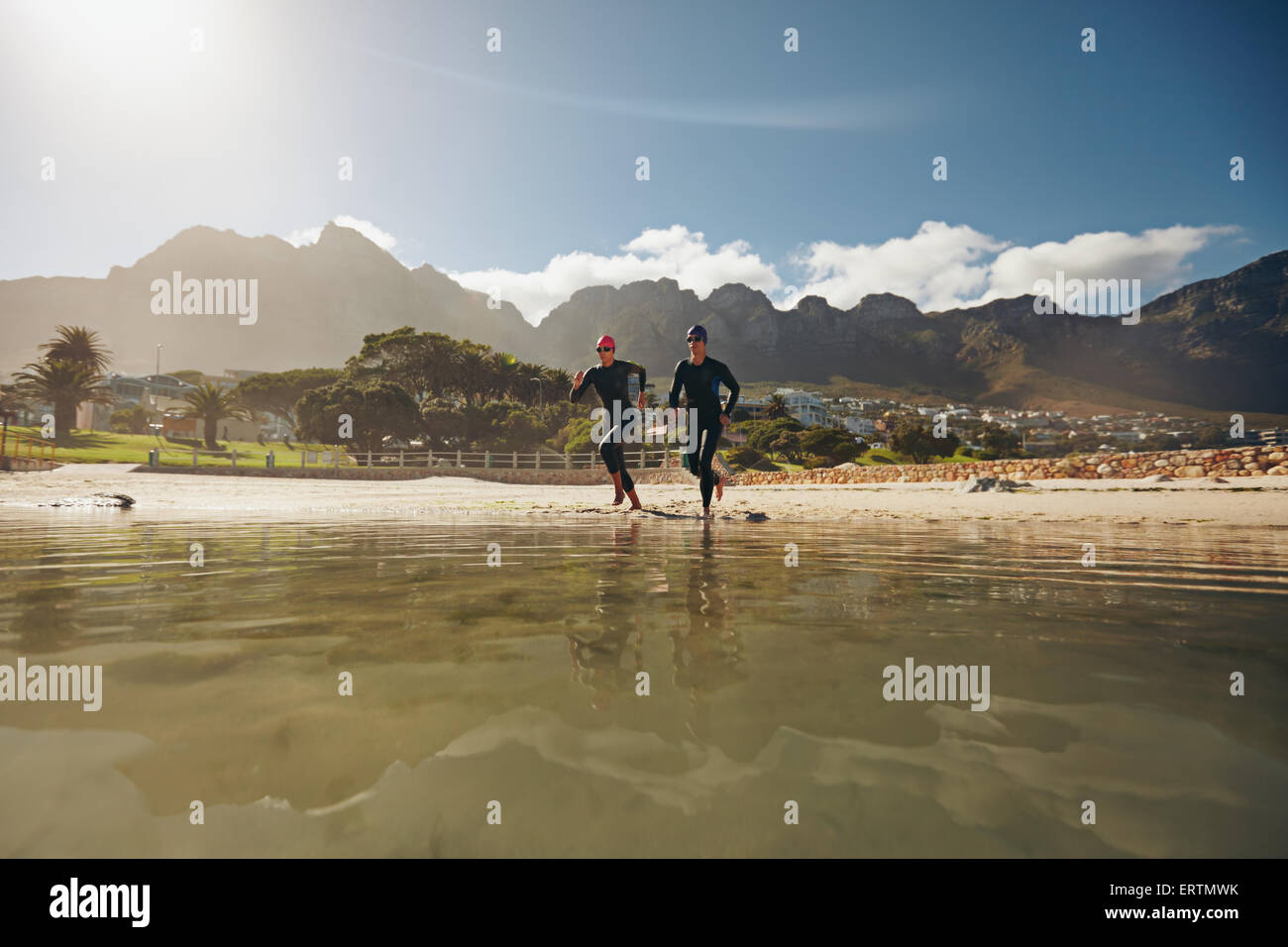 Shot of two athletes running into the water, practicing for triathlon competition. Young man and woman in wet suits - Stock Image