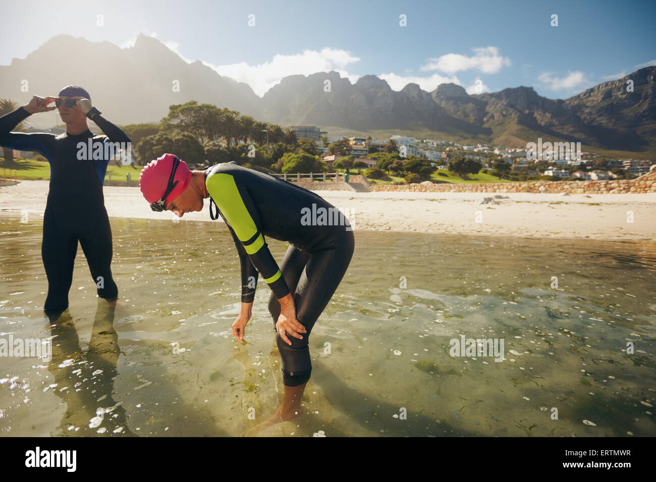 Athletes resting after triathlon training session. Young man and woman standing in water taking a break from practicing. - Stock Image
