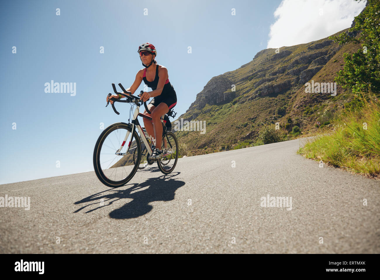 Woman competing in the cycling leg of a triathlon with competitor. Triathletes riding bicycle on open road. - Stock Image