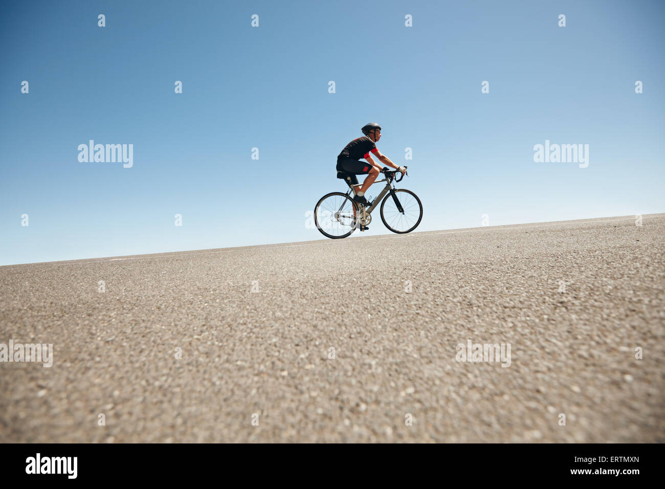 Low angle image of a male cyclist riding on a flat road against blue sky. Man cycling up hill on open road. - Stock Image