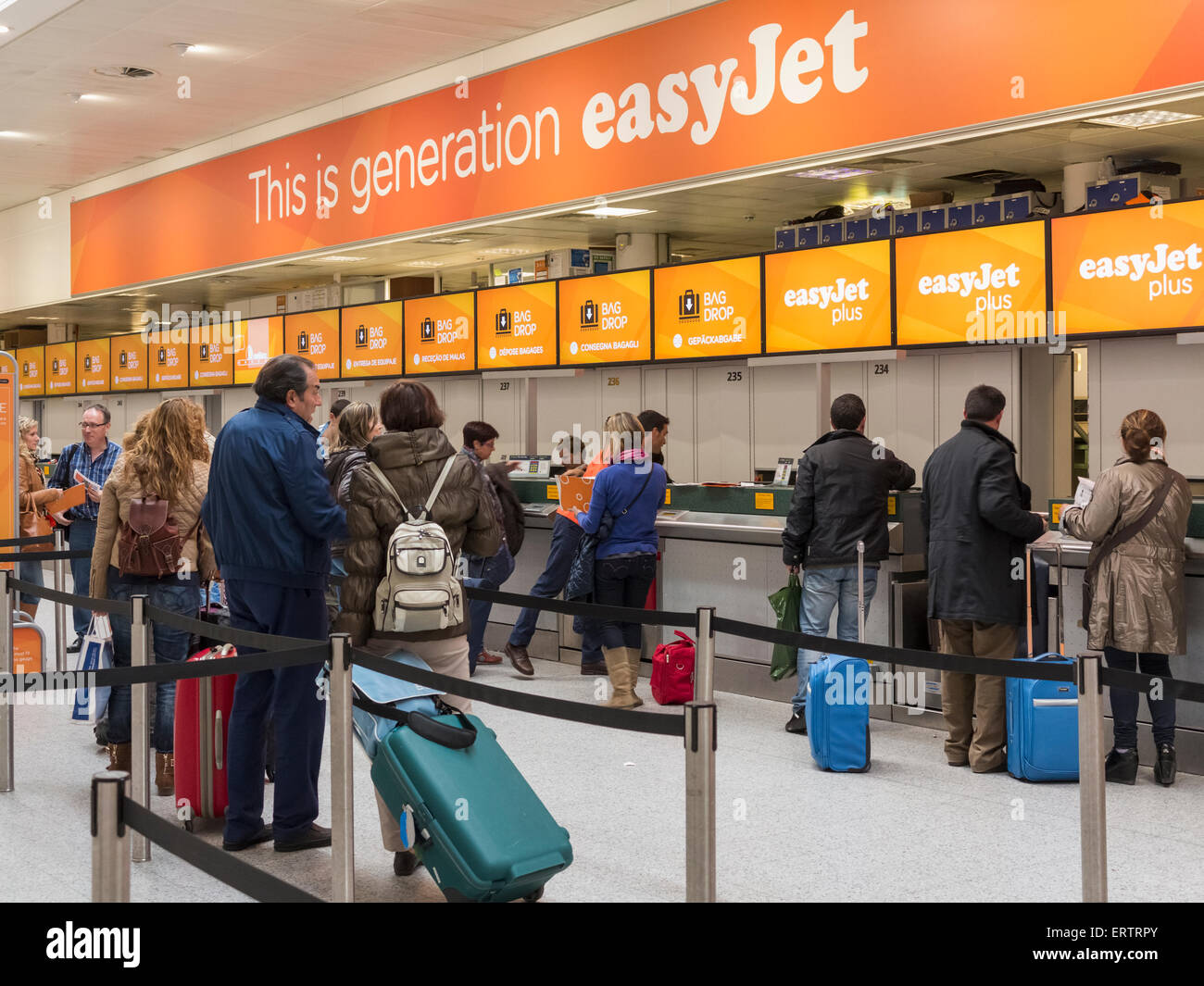 The Easy Jet budget airline check-in desk at Gatwick Airport, London, England, UK - with a line of people queuing - Stock Image