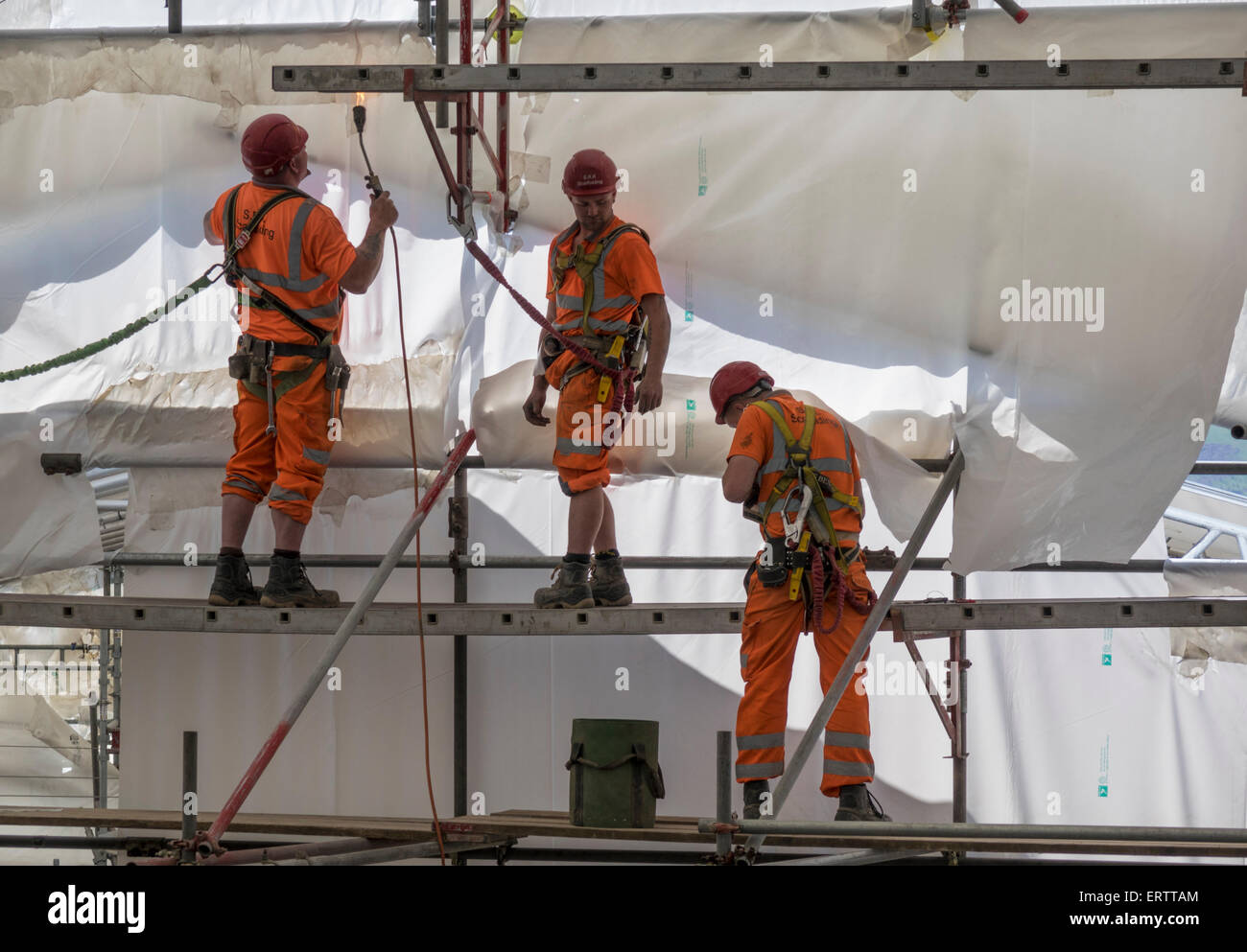 Construction workers erecting scaffolding and encasing it in plastic tent for protection from weather, UK - Stock Image