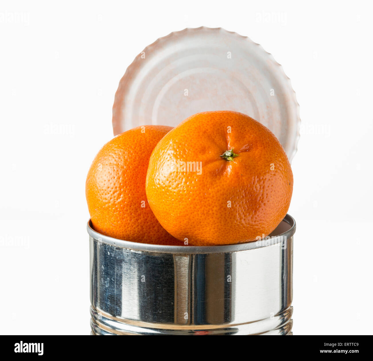 Oranges / satsumas fruit heaped inside opened tin can - fresh food coming in cans concept - Stock Image