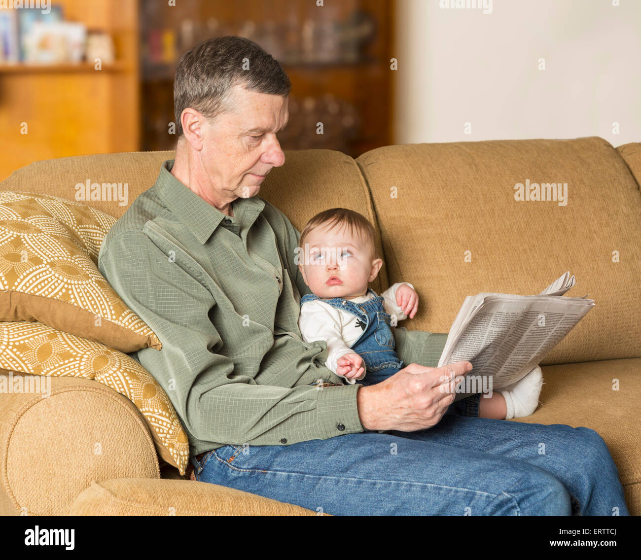 Baby girl and grandfather reading newspaper on settee in family living room - Stock Image