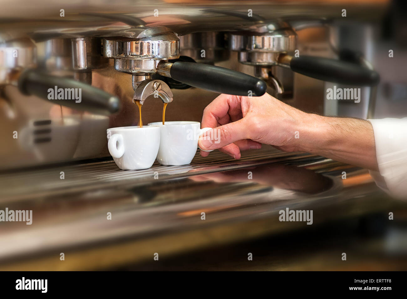 Close up view of the hand of a man working in a coffee house preparing espresso coffee - Stock Image