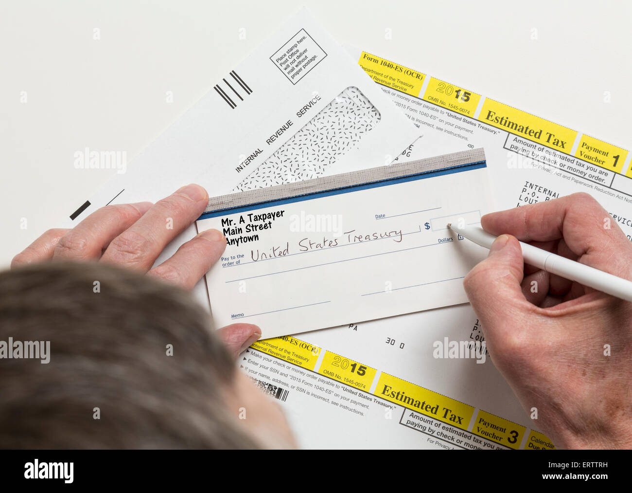 Man writing check to Internal revenue service IRS form 1040-ES for payment of estimated taxes in 2015 - Stock Image