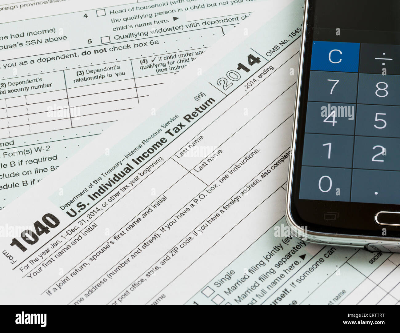 USA tax form 1040 with calculator app on phone - Stock Image