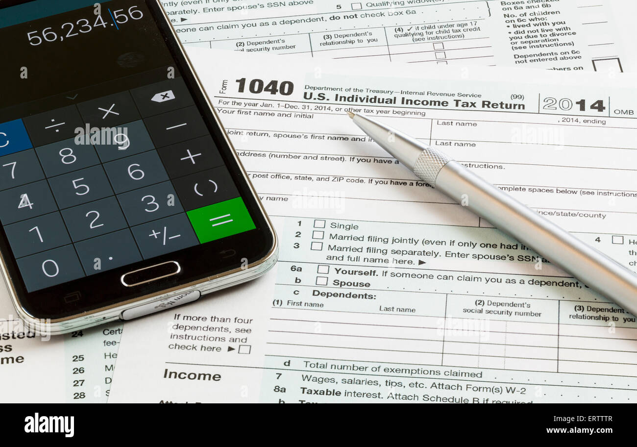 USA tax form 1040 with a pen and calculator app on smartphone completion of tax forms for the IRS - Stock Image
