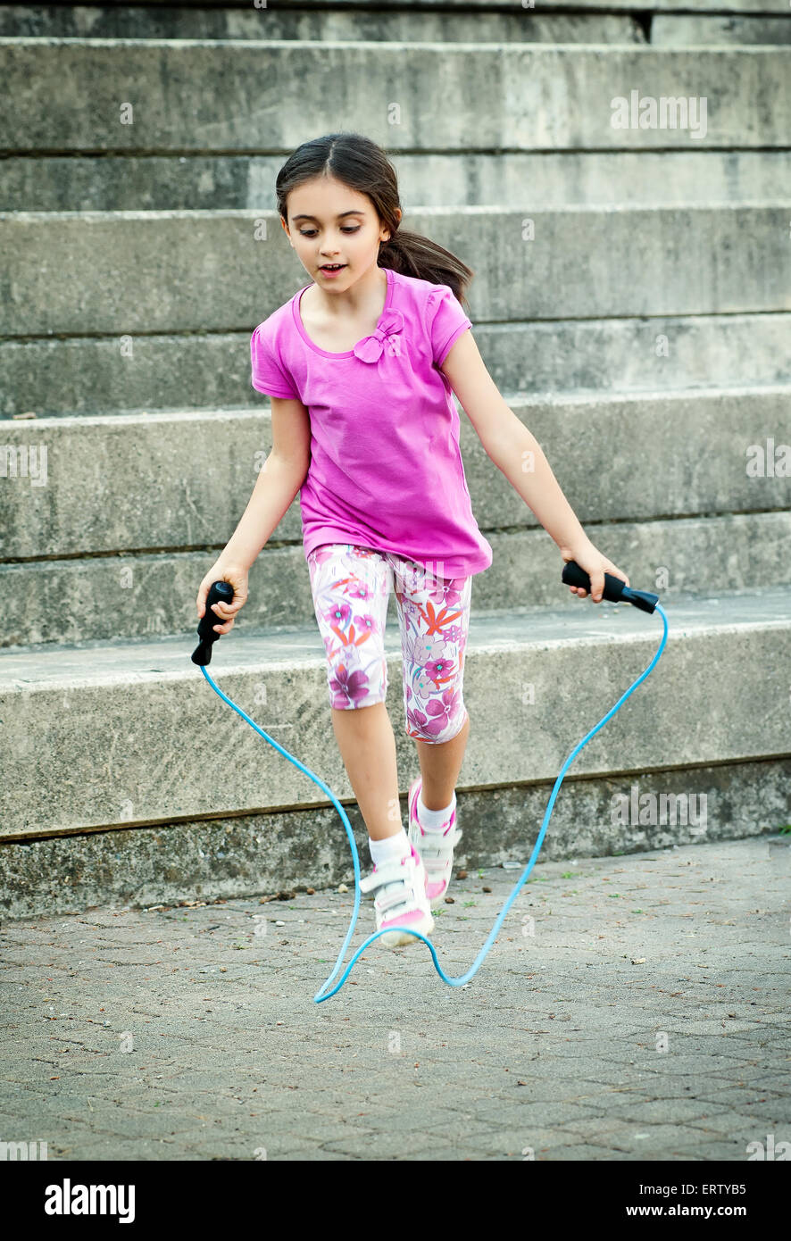 Happy attractive little girl in a trendy pink outfit skipping outdoors - Stock Image