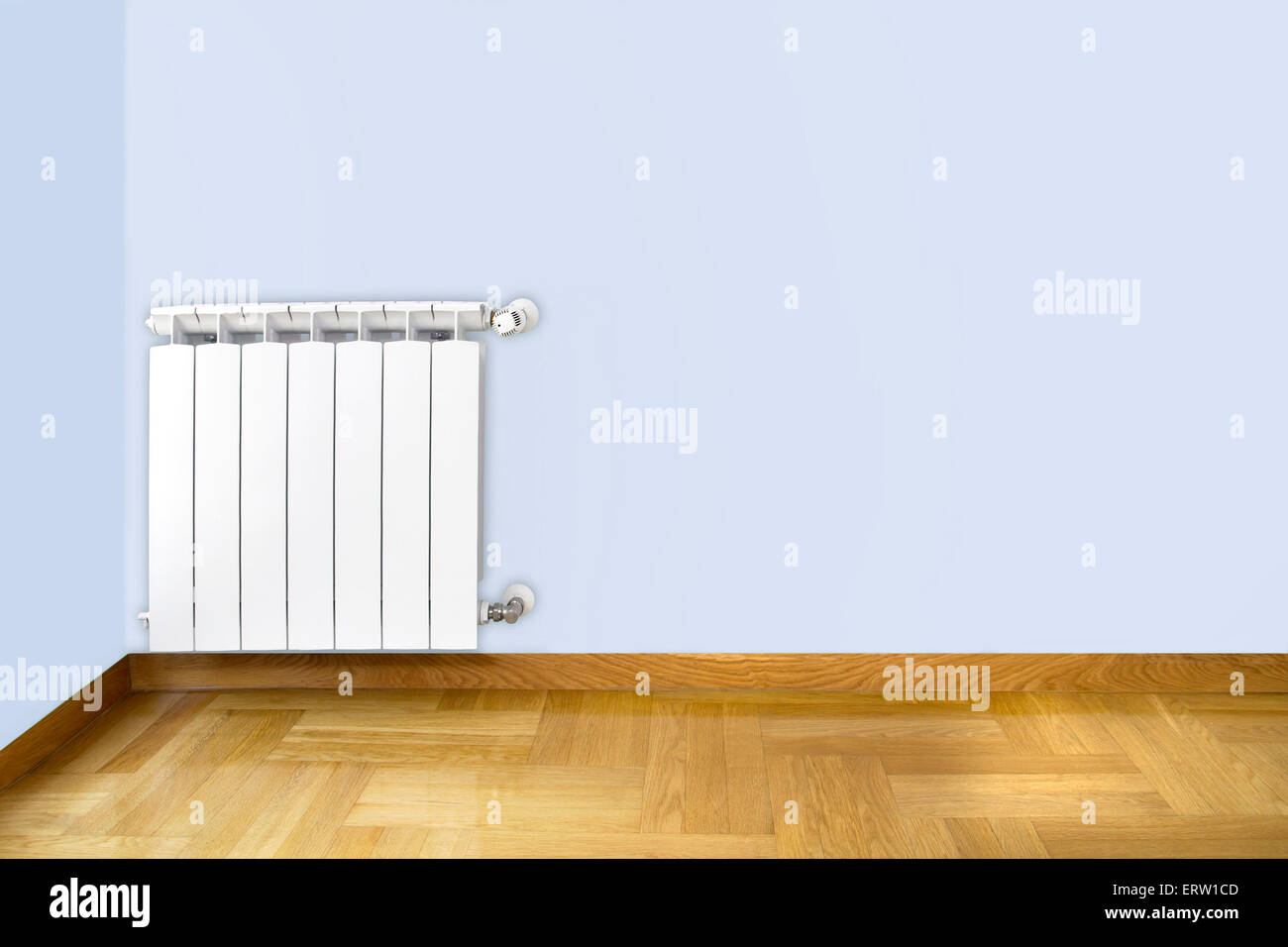White heating radiator on blue wall and wooden parquet floor Stock ...