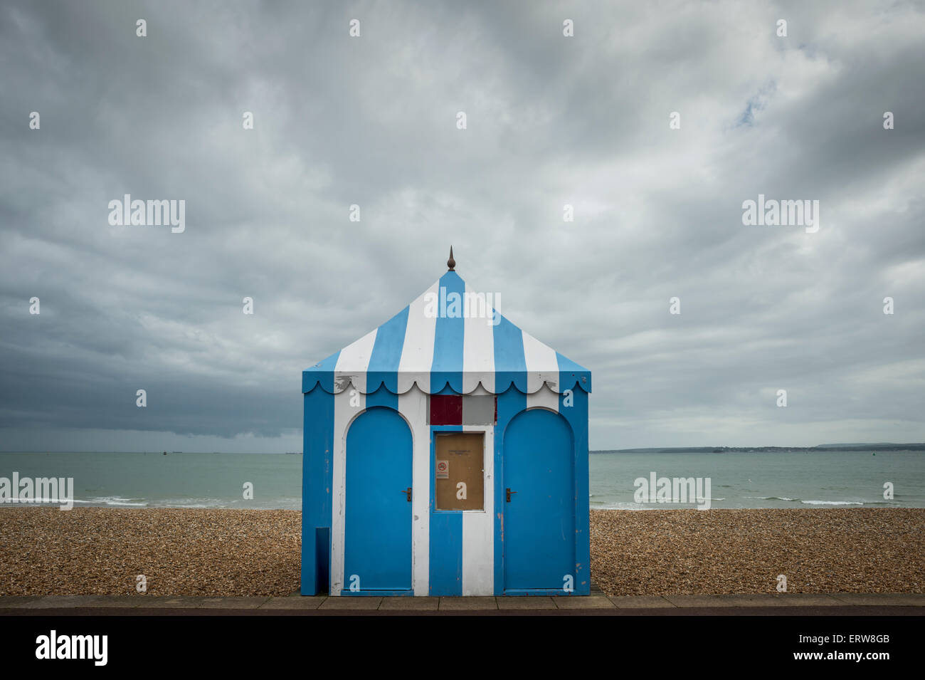 blue & white striped hut on the seafront on a stormy day - Stock Image