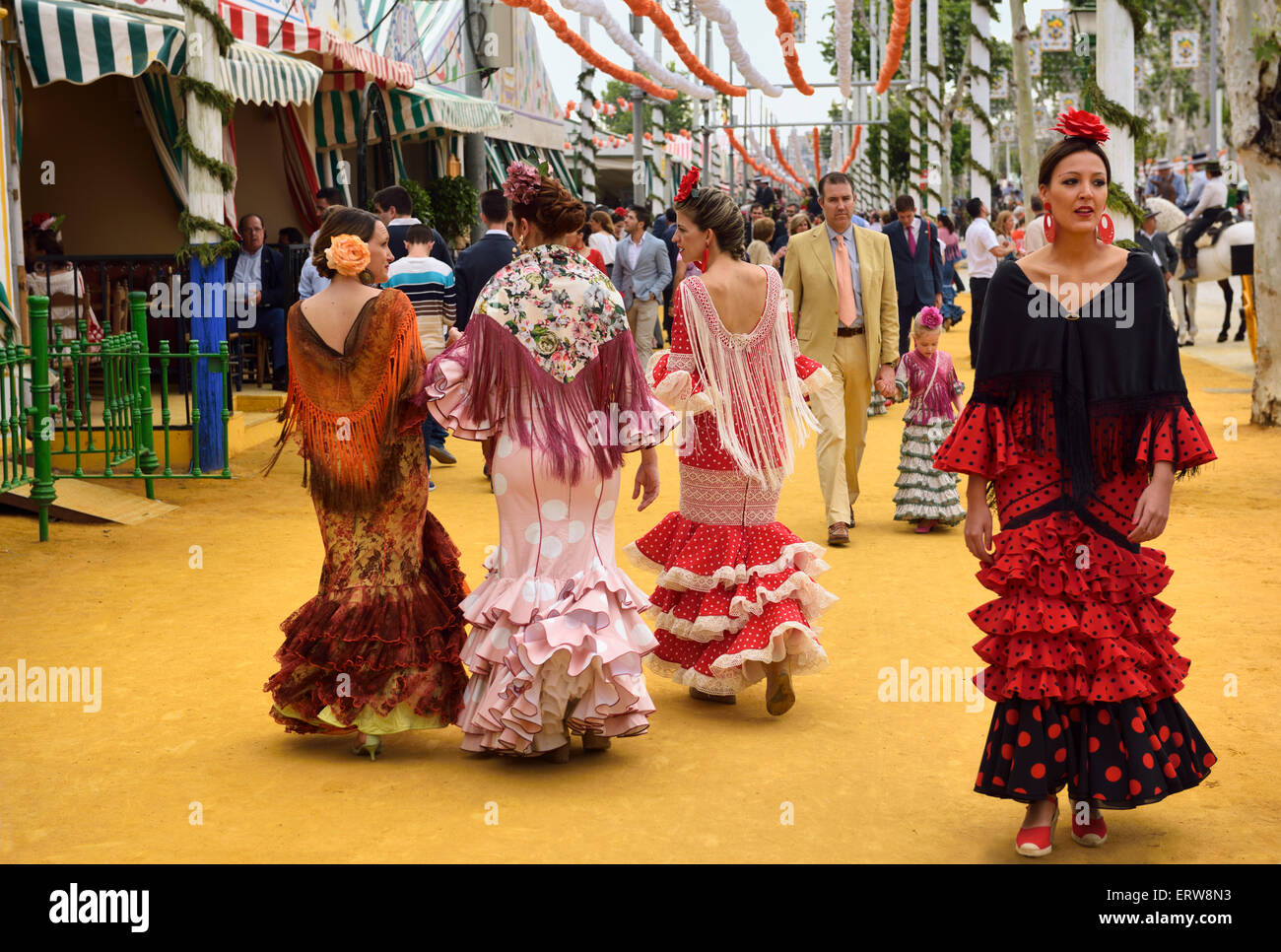 Women in flamenco dresses walking on ochre earth at the April Fair in Seville Spain - Stock Image