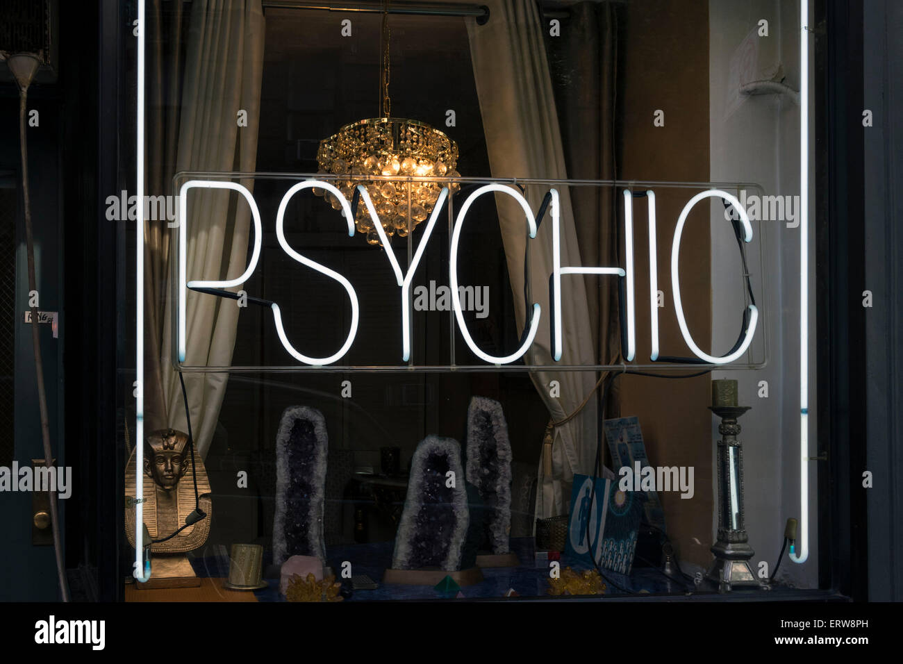 A neon window sign advertises a psychic or fortune teller for consultations - Stock Image