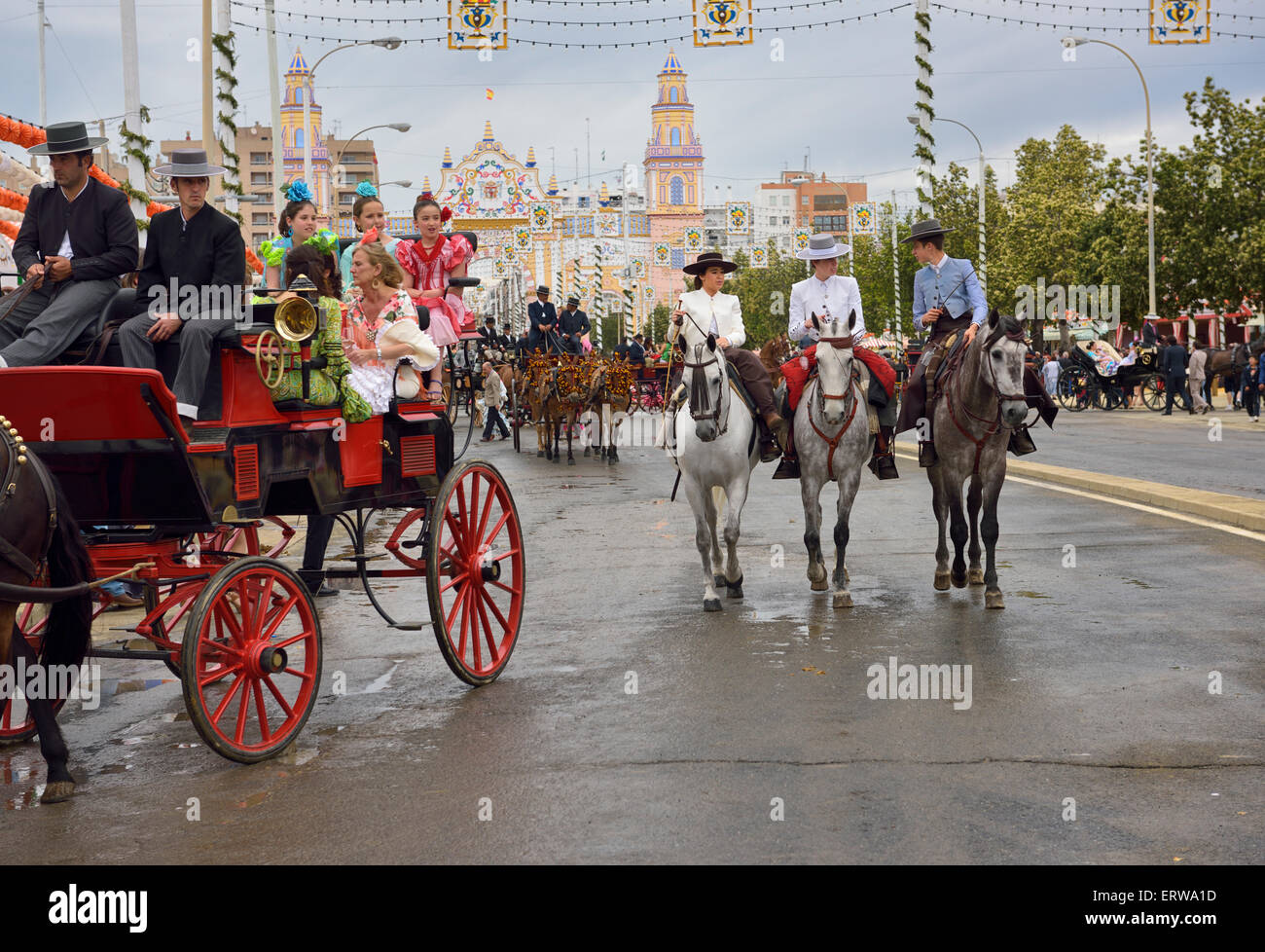 Mule drawn carriages and horseback riders on Antonio Bienvenida street with Main Gate 2015 Seville April Fair Spain - Stock Image