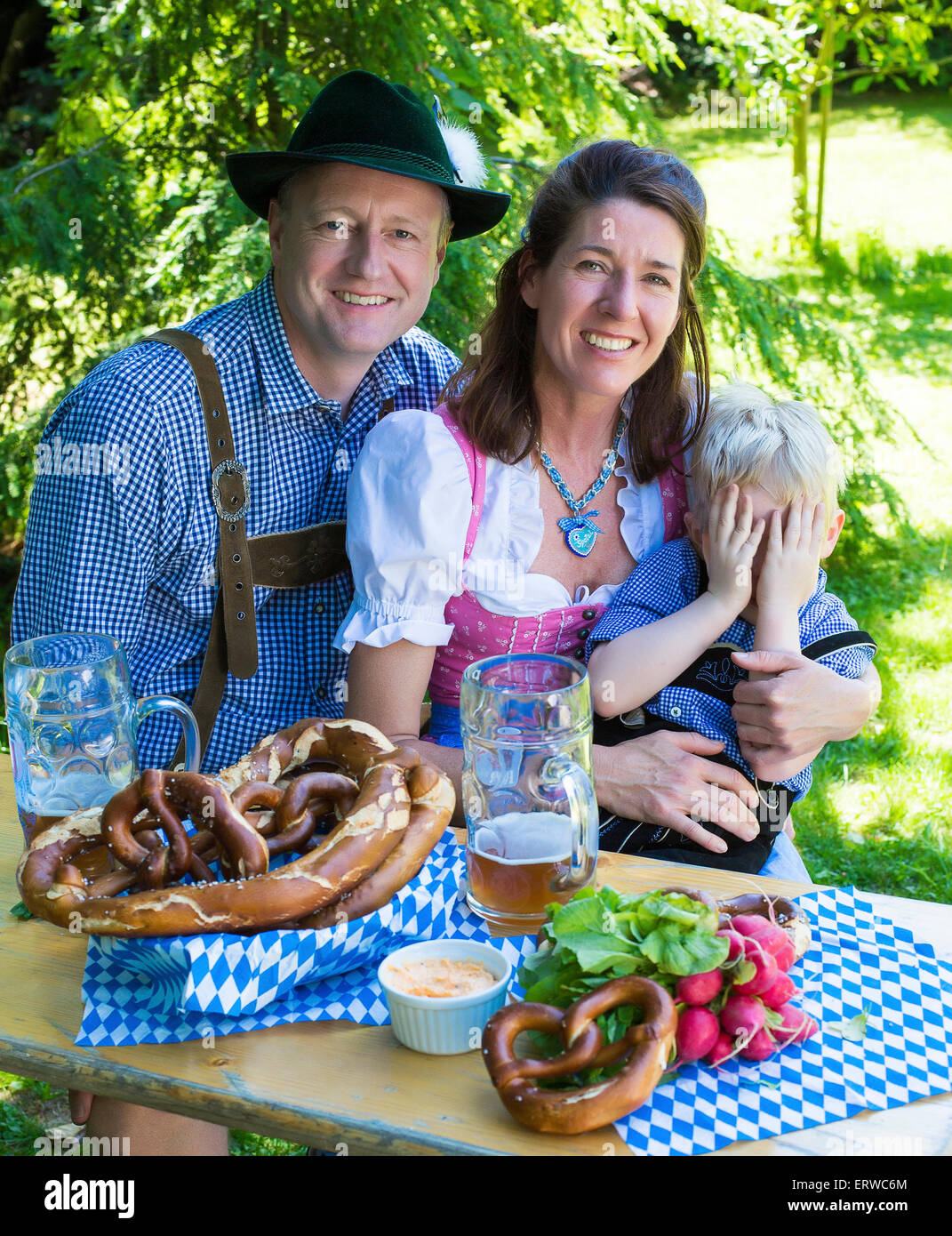 bavarian family sitting outside on a bench and smiling Stock Photo