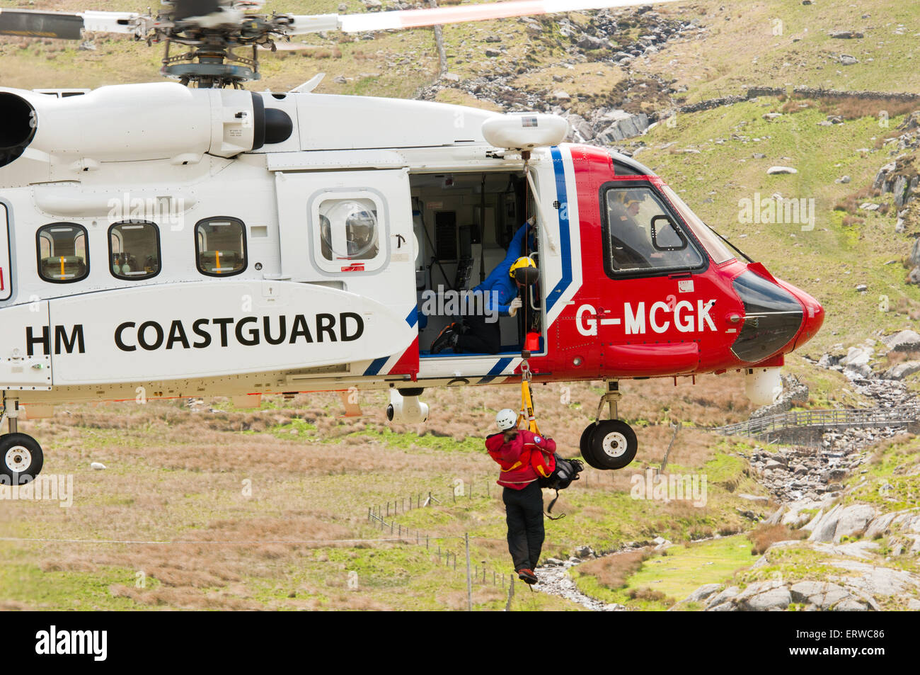 A mountain rescuer is winched into a skillfully hovering Sikorsky S-92 helicopter operated by Bristow for HM Coastguard Stock Photo
