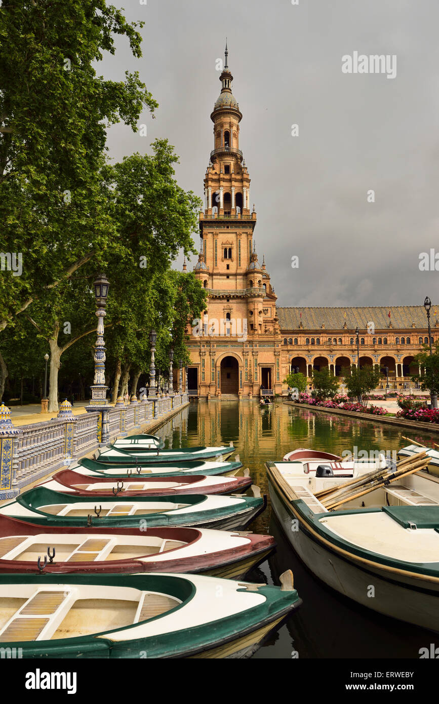 Row boats in canal with North tower at Plaza de Espana Seville Spain - Stock Image