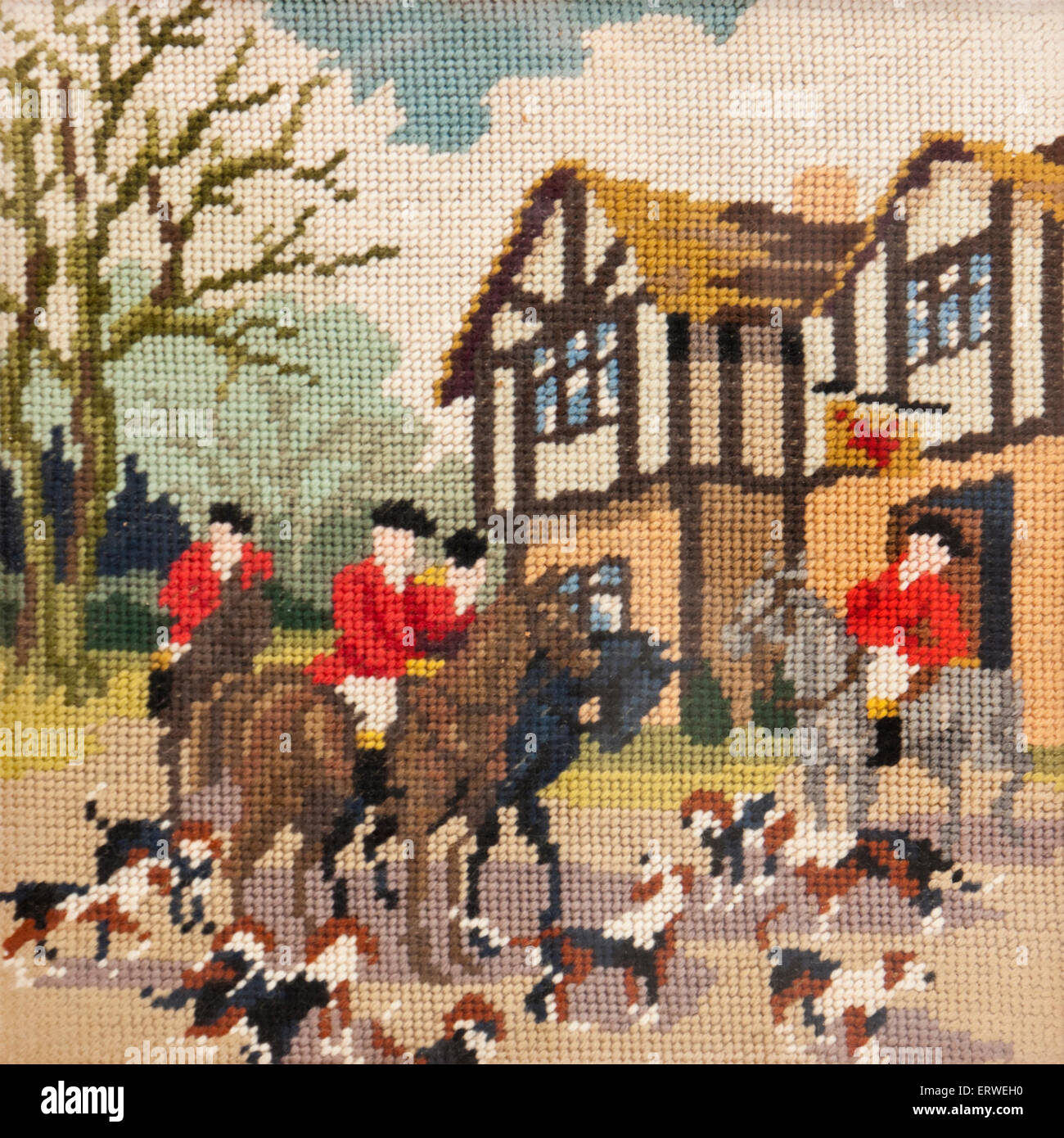 Cross stitch / needlework of a fox hunting scene in a village - Stock Image