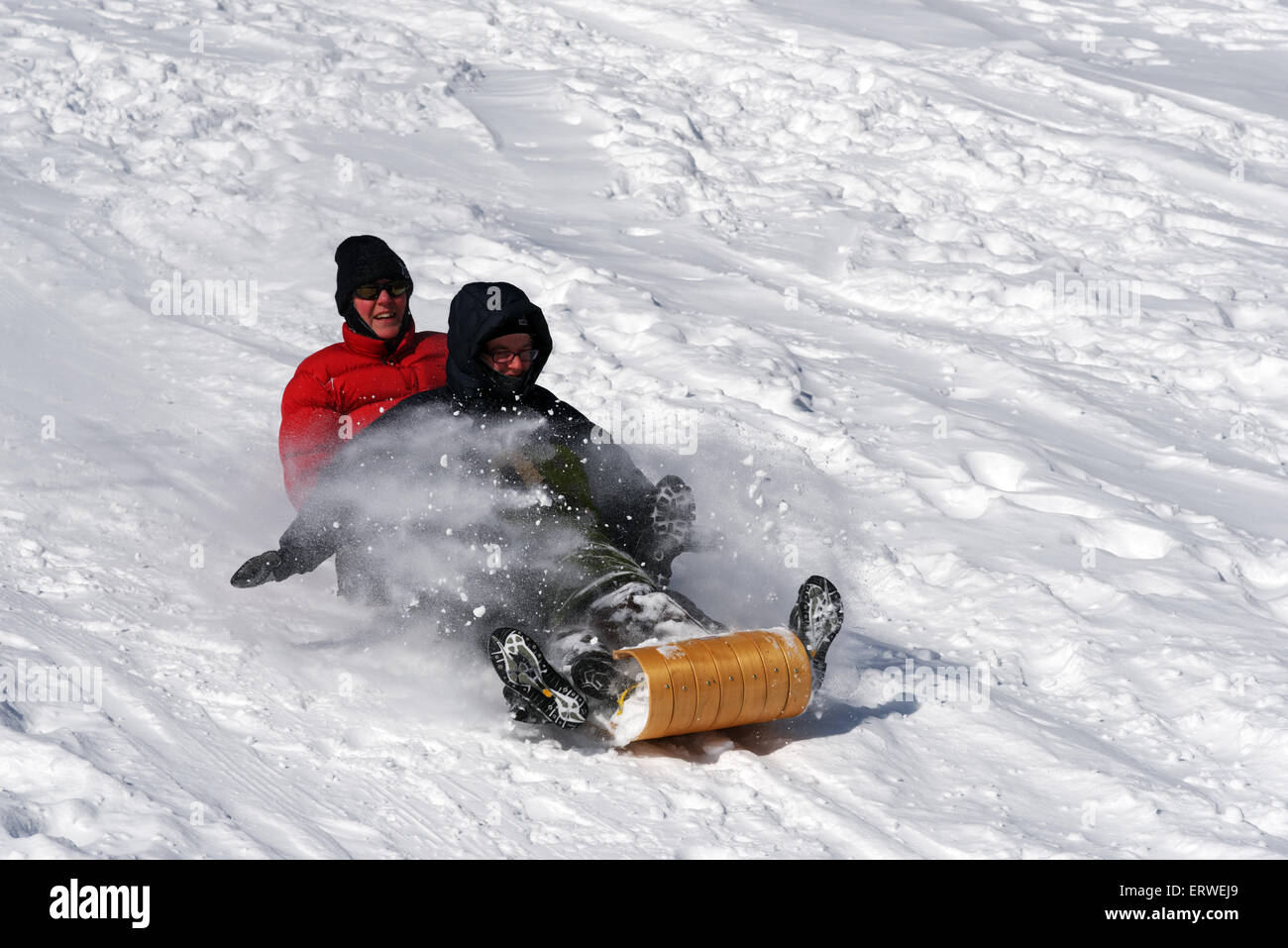 Two women laughing on a sledge - Stock Image