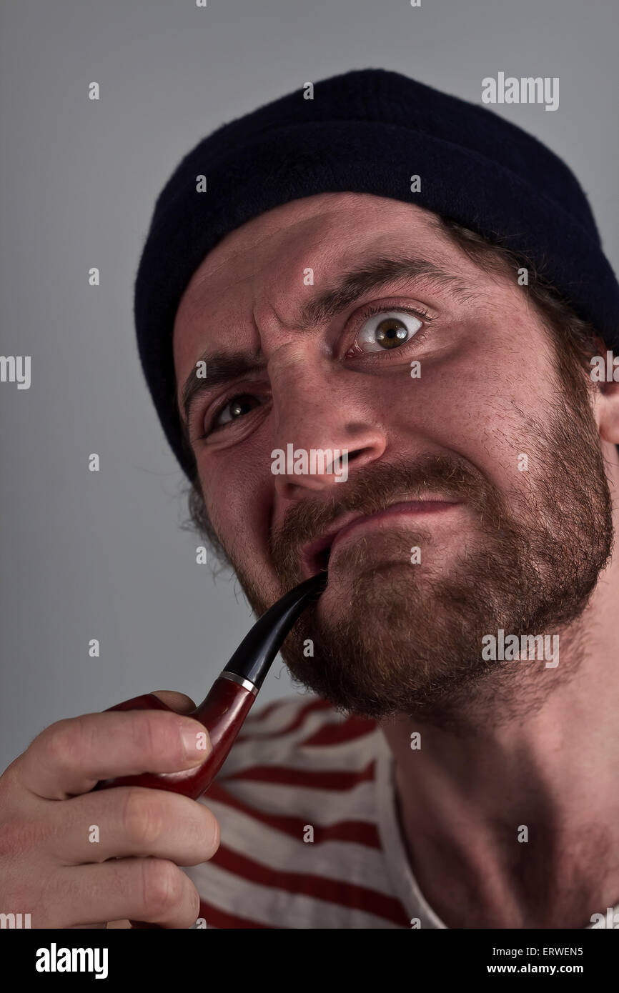Mean bearded sailor grimacing while smoking a pipe - Stock Image