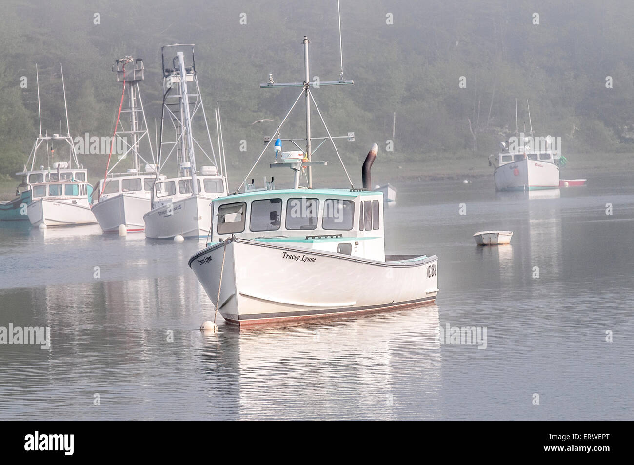 This foggy fleet of fishing boats sit at their mooring until the fog burns off enough so the fishermen can set out - Stock Image