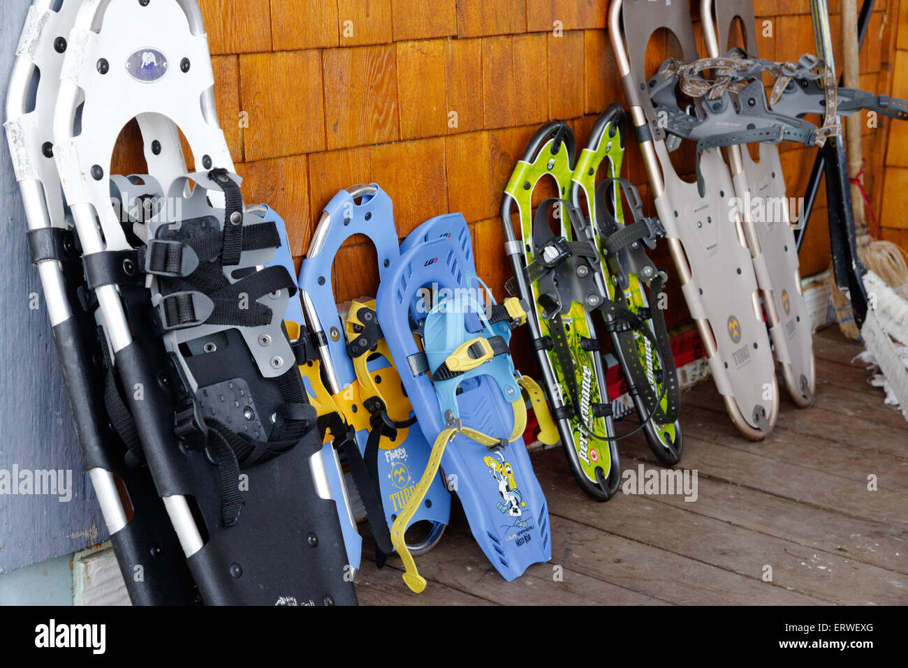 A family's snowshoes on the balcony of a house - two adult and three children's pairs. - Stock Image