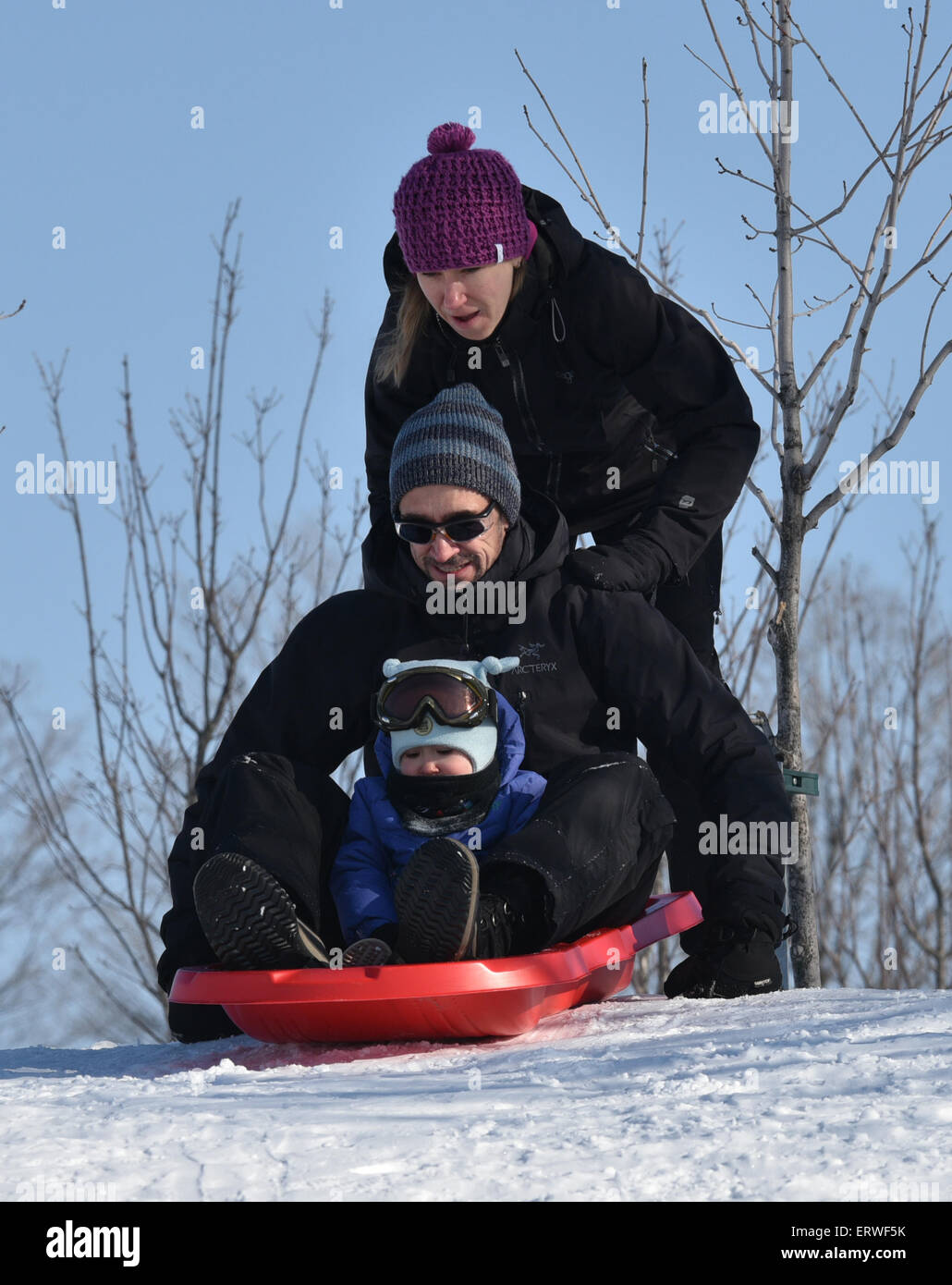 Mother pushing father and daughter on a sledge - Stock Image