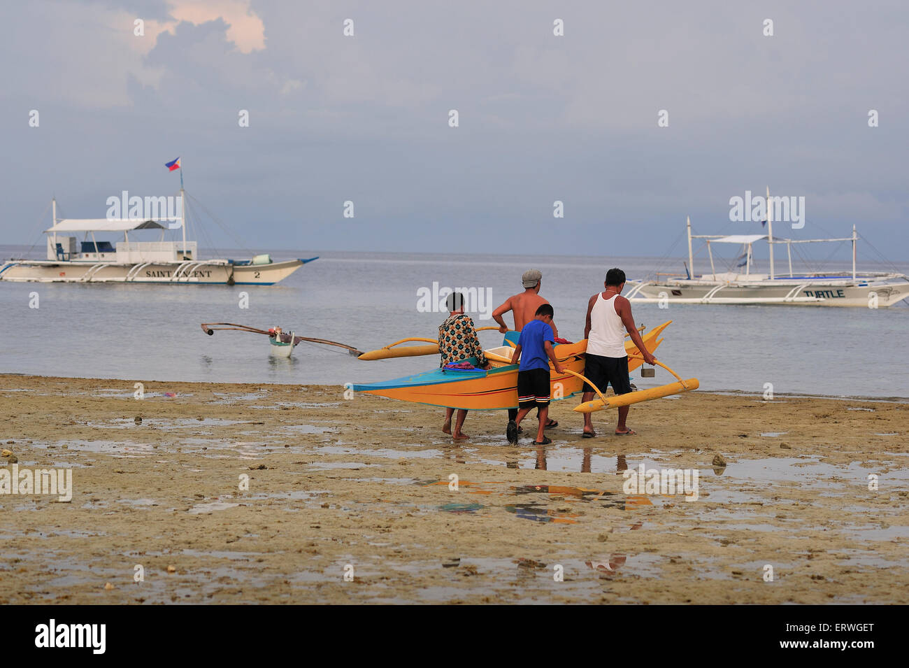Young Filipinos carrying fishing boat to water's edge Panagsama Beach Moalboal Philippines - Stock Image