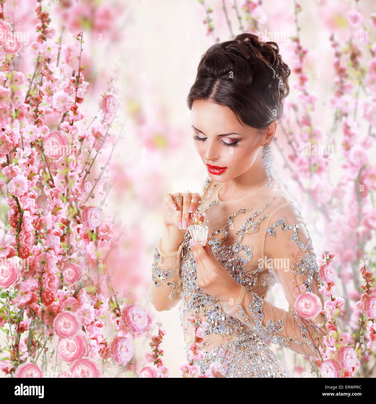 Woman with Perfume over Floral Background - Stock Image
