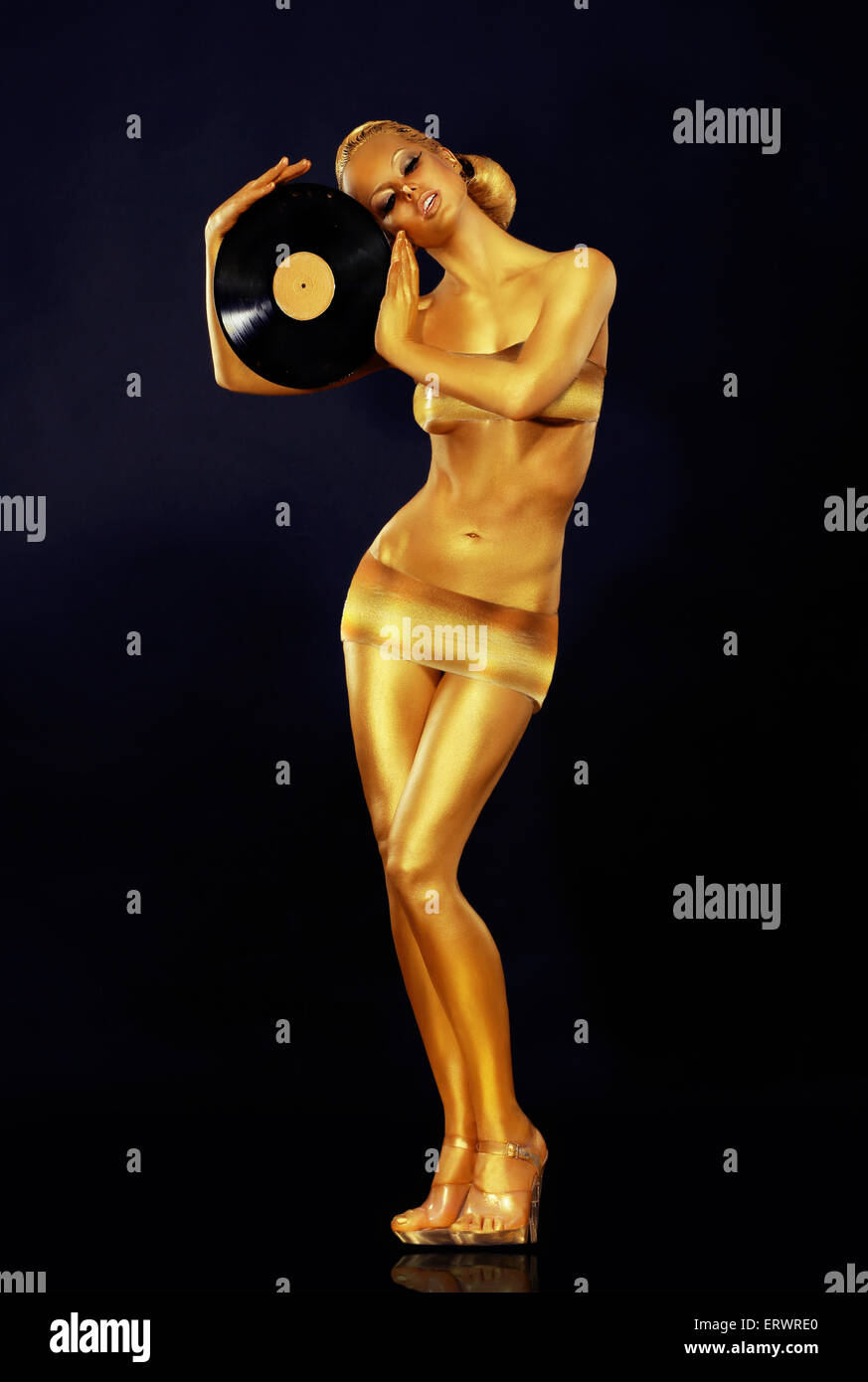 Woman Painted Gold With Vinyl Record - Stock Image