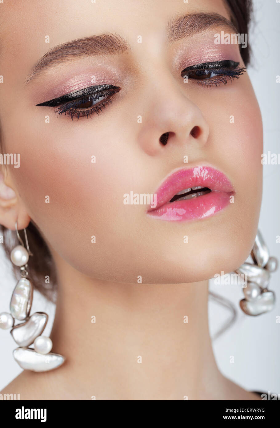 Studio Portrait of Young WOman with Earrings - Stock Image