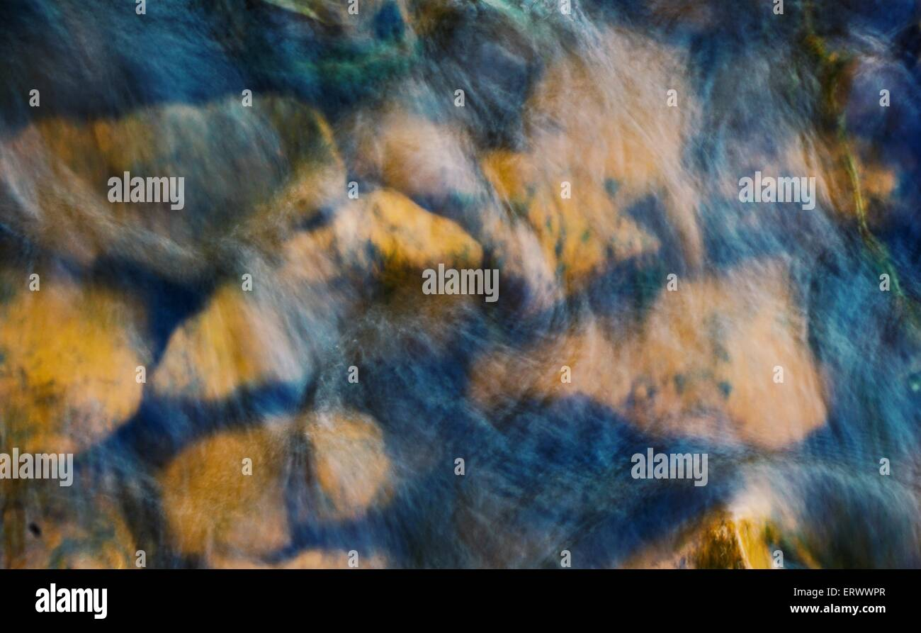Moving water in river over rocks. - Stock Image