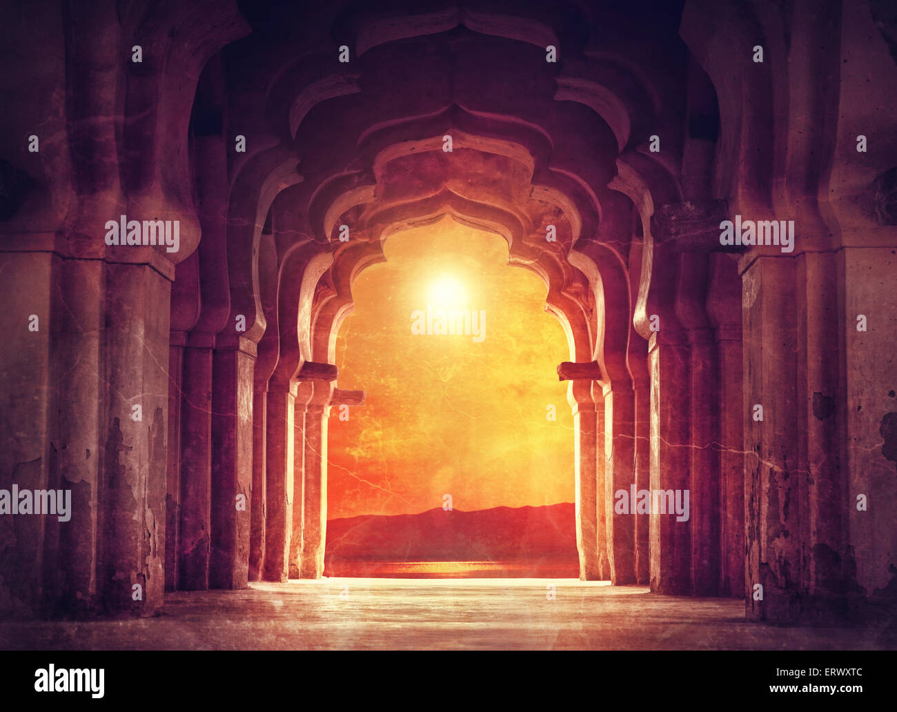 Old ruined arch in ancient temple at sunset in India - Stock Image