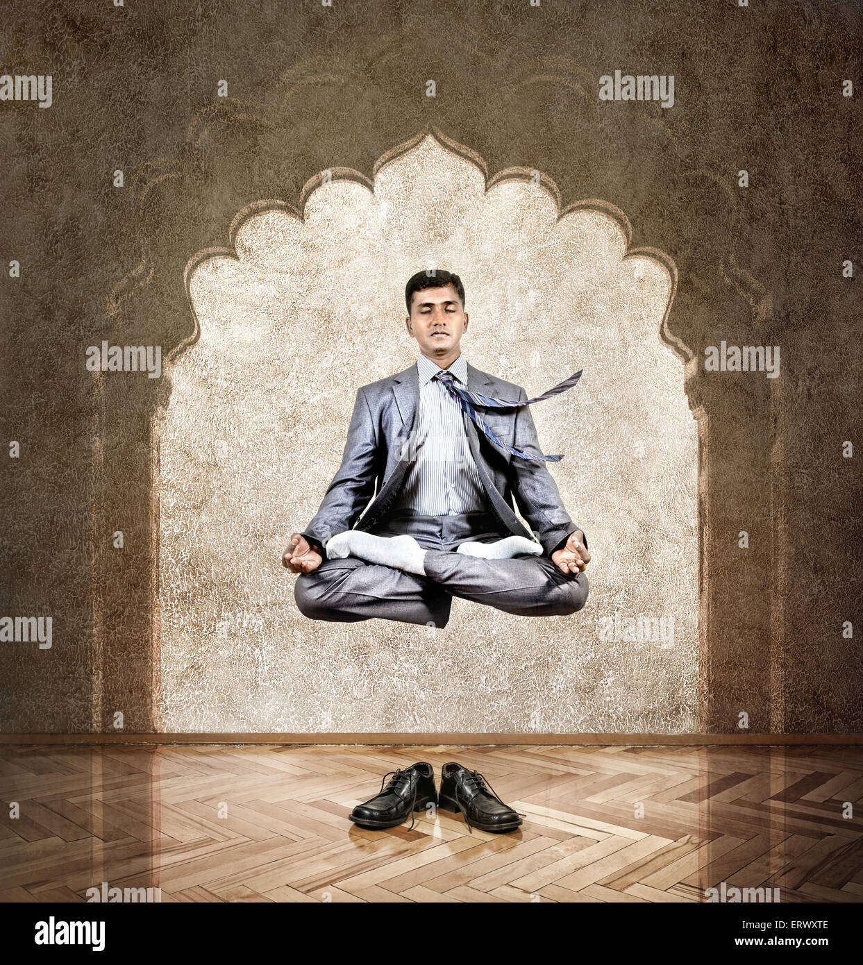 Indian businessman doing meditation in the air in lotus pose at the office with arch on the wall - Stock Image