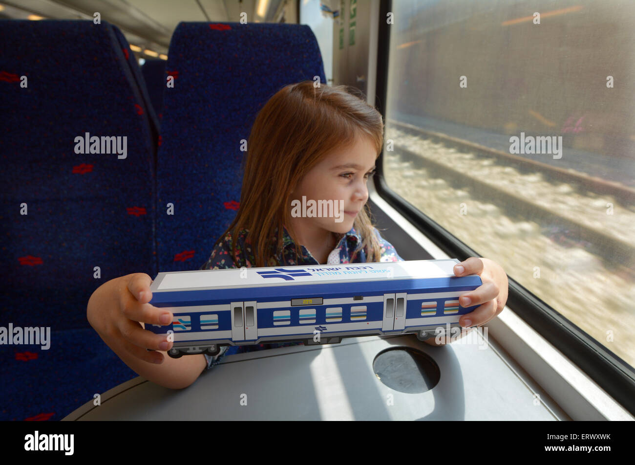 TEL AVIV - APR 05 2015:Little girl (talya Ben-Ari age 05) hold a model of Israel Railways train.It's state-owned - Stock Image