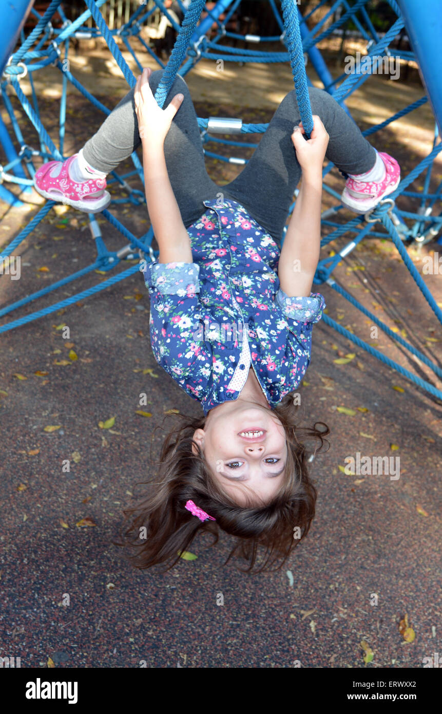 Little child (girl age 05) play on spider web bar in a outdoor playground - Stock Image