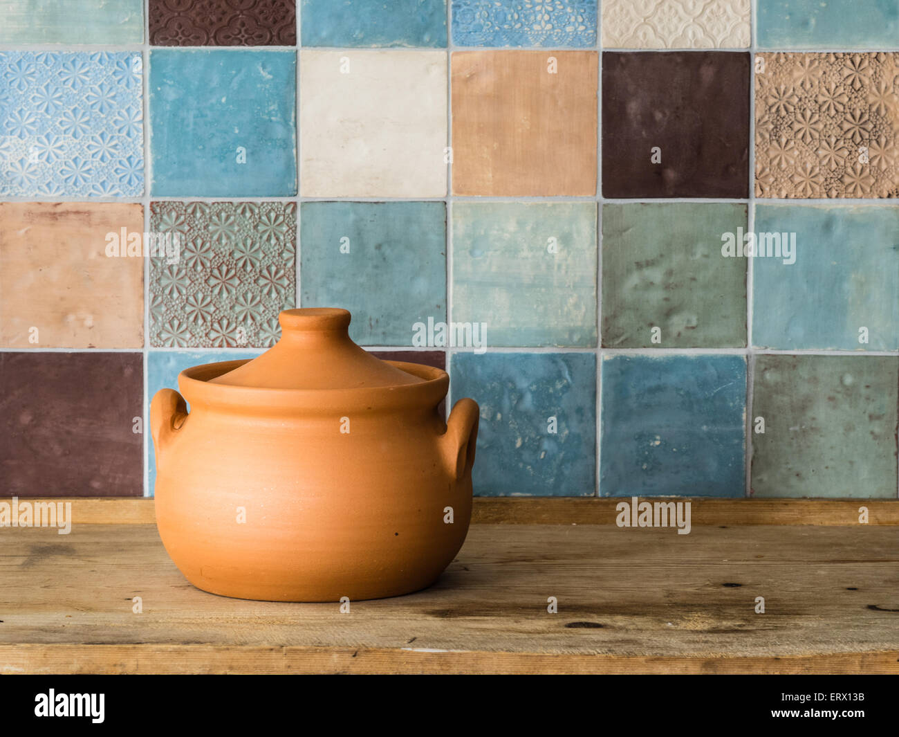 handmade ceramic pot in front of a colorful tiled wall in a countryside kitchen - Stock Image