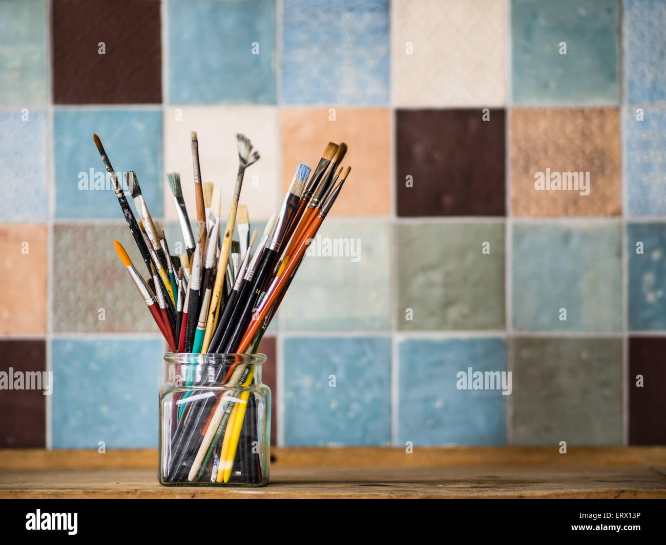 Bunch of paint brushes in a glass jar in front of a colorful tiled wall - Stock Image