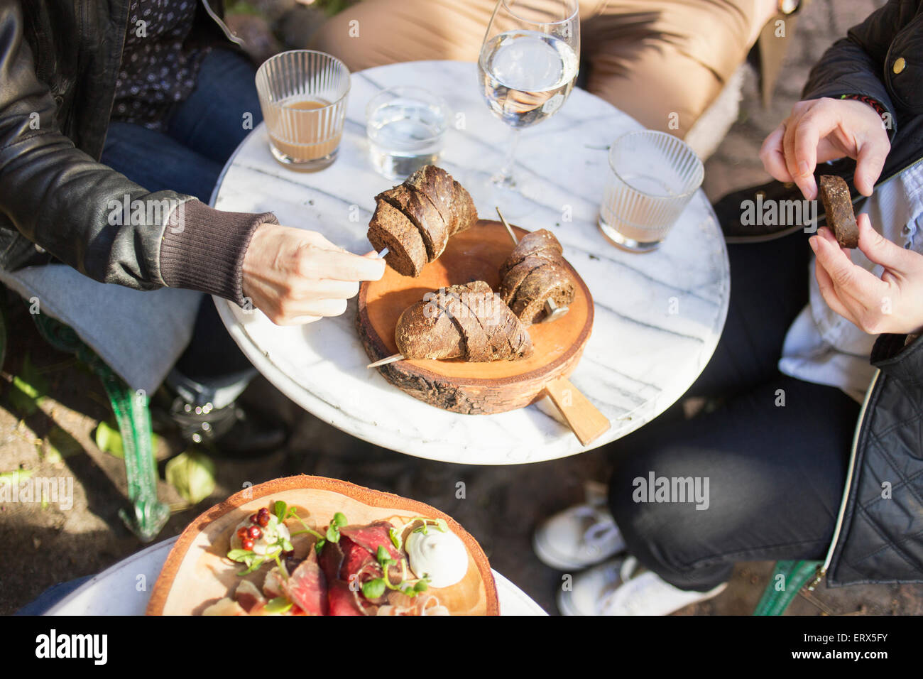 High angle view of hands holding bread slices at outdoor cafe - Stock Image