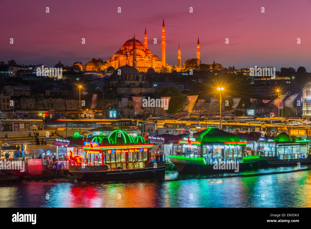 Boat restaurants floating on the Golden Horn with Suleymaniye Mosque behind at dusk, Istanbul, Turkey Stock Photo