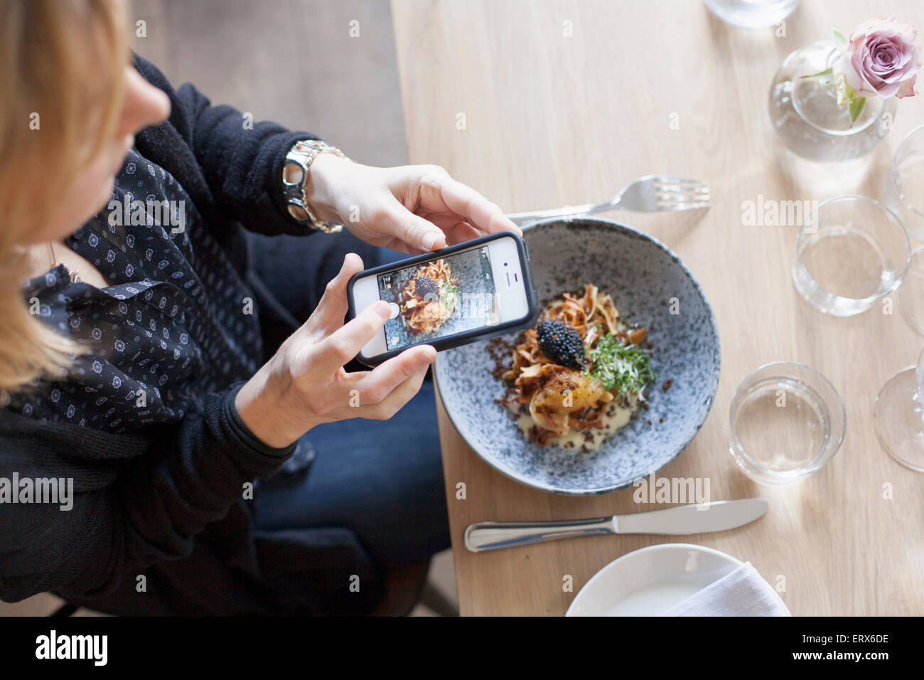 High angle view of woman photographing food through mobile phone in restaurant - Stock Image